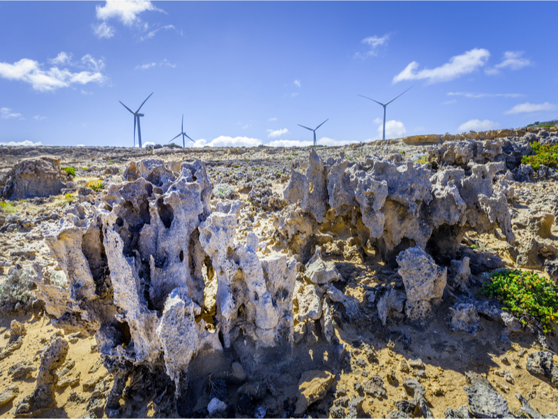 Weathered rock formations and wind turbines - renewable energy and earth conservation concept-by Greg Brave_shutterstock_754368991