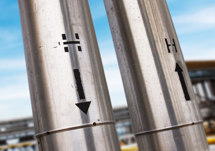 Grey metal Technological tubes and pipelines with arrows and Hydrogen signs. Close-up. Petrochemical industry. Oil refinery and gas processing plant.