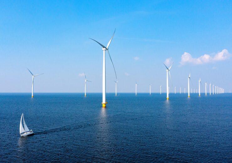 Windturbines and sailboat in sea